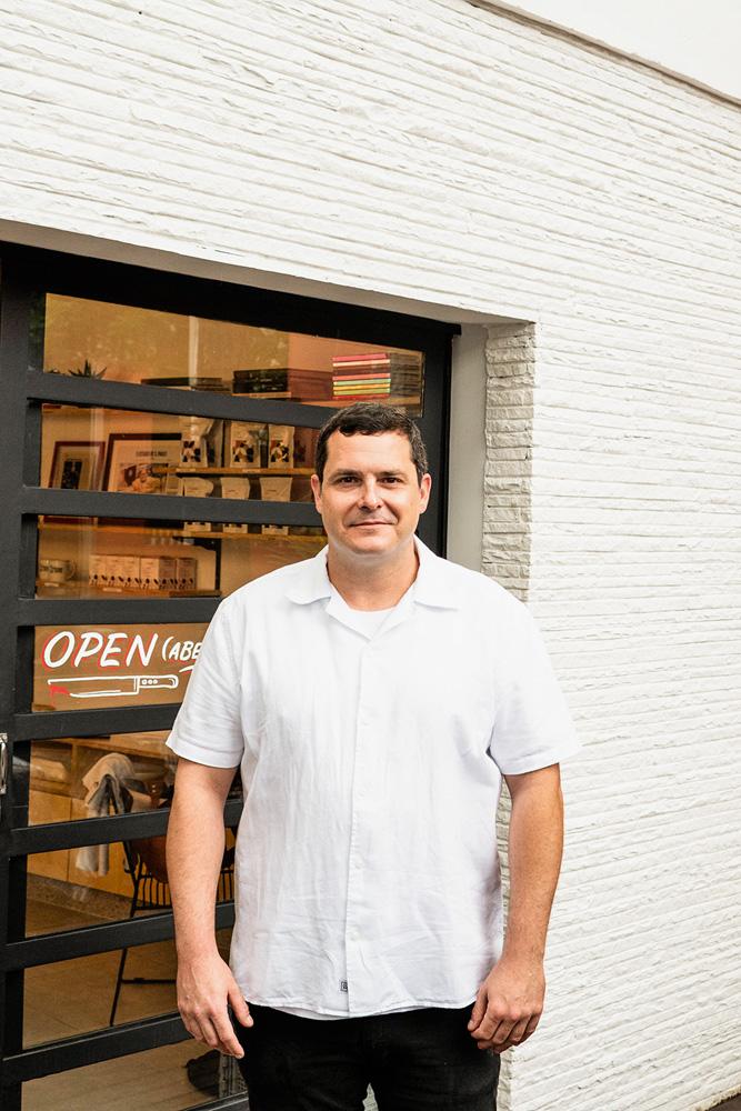 Homem ao centro (Rafael Protti) vestindo uma camisa branca larga com meio sorriso em frente à fachada da Crime Pastry Shop.