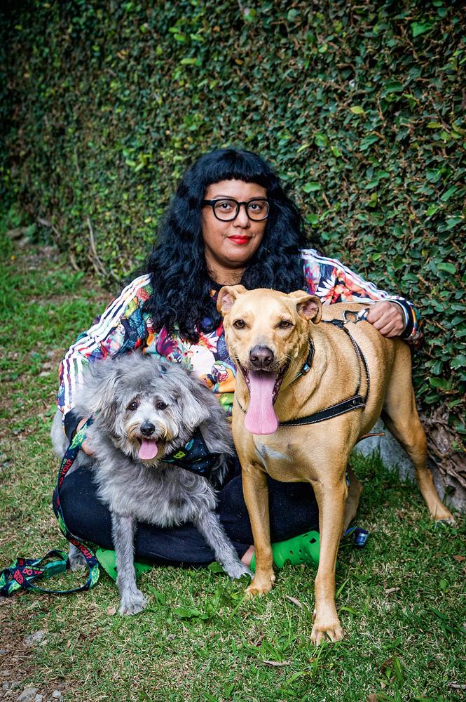 Uma mulher de cabelos bem pretos abraça dois cachorros, um cinza e um amarelo, na grama