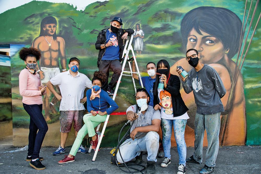 artistas responsáveis pela reforma posando para a foto à frente de um dos murais