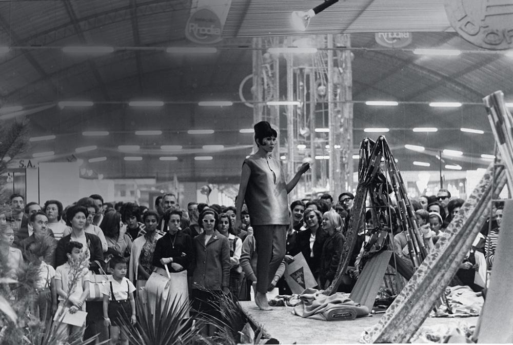 A imagem em preto e branco mostra a modelo em uma passarela no meio da feira de automóveis. O local está lotado de pessoas.