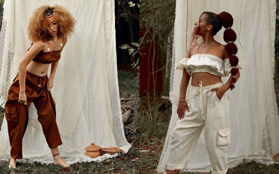 Montagem com menina que posa em frente a um lençol branco estendido. Tem cabelo crespo ruivo e veste um top e uma calça vinho. Outra menina posa em frente a um lençol branco estendido. Tem cabelo crespo vermelho preso e veste top e calça branca