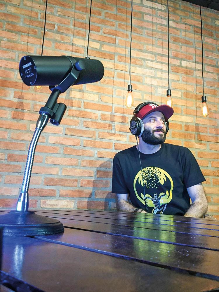 A imagem mostra Dinho Lima, em frente à uma mesa de madeira, com um microfone sobre ela