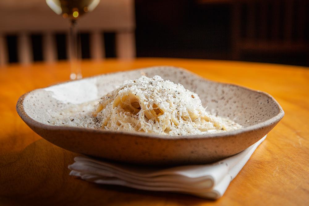 Espaguete cacio e pepe em um prato de cerâmica sobre guardanapo branco dobrado em cima de mesa de madeira.