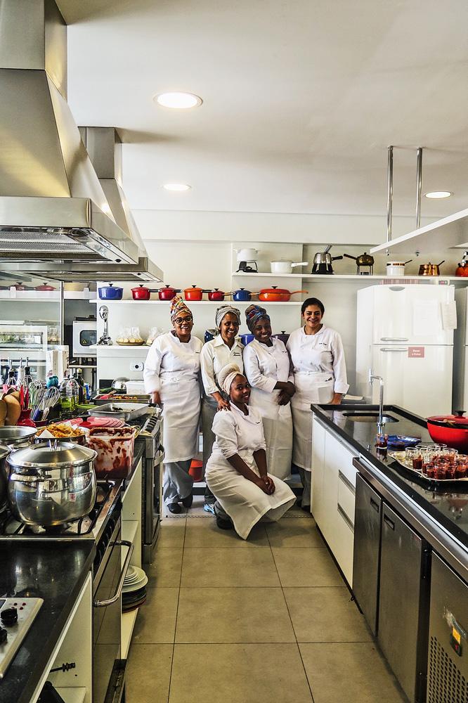 Numa cozinha industrial, ao fundo, aparecem cinco mulheres de dólmã e avental. Quatro estão em pé e uma ajoelhada ao centro para a foto. Todas sorrindo.