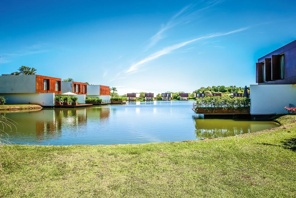 Imagem é um retrato amplo de uma área externa do condomínio de luxo. Há grama, um lago e grandes casas nas margens.