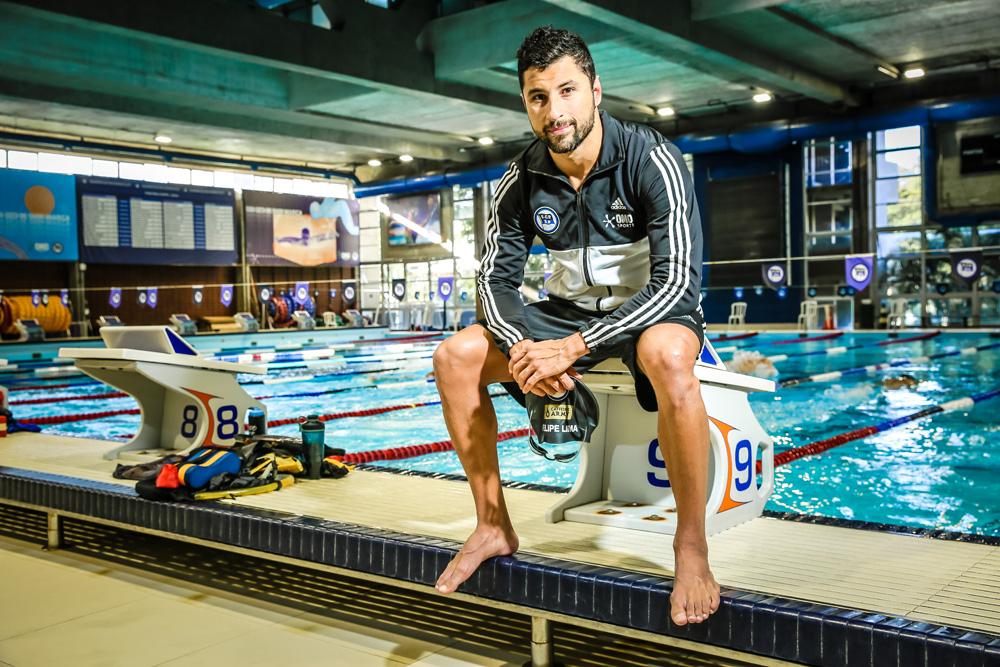 A imagem mostra Felipe sentado na beira da base de um trampolim, olhando com um sorriso tímido para a câmera