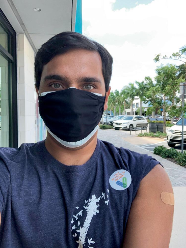 fábio posao para a foto logo após ser vacinado. ele está usando máscara de proteção e exibe o braço esquerdo com um pequeno band-aid.