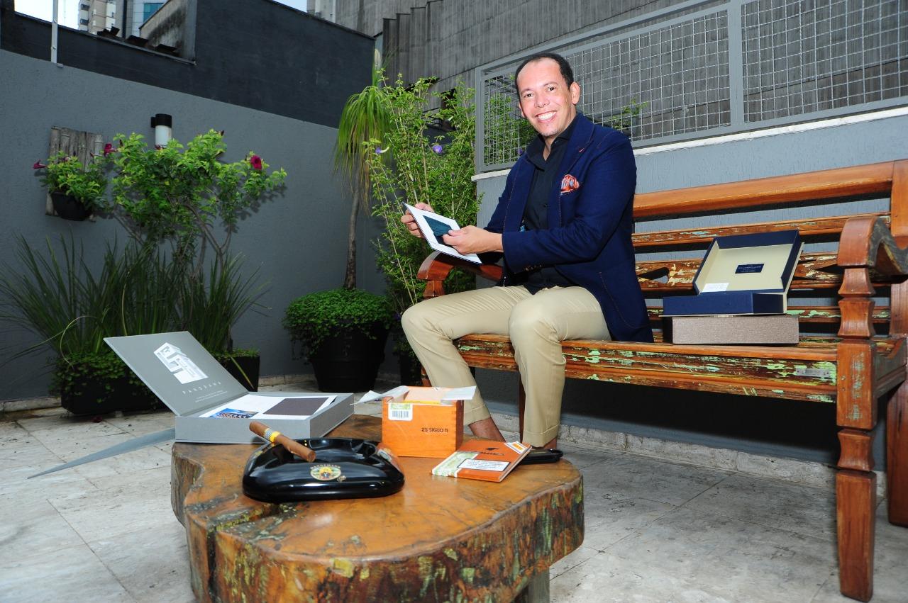 O alfaiate Fabrizio Allur posa sentado em banco de madeira com caixa de charutos na sua frente. Veste calça bege e paletó azul-marinho.