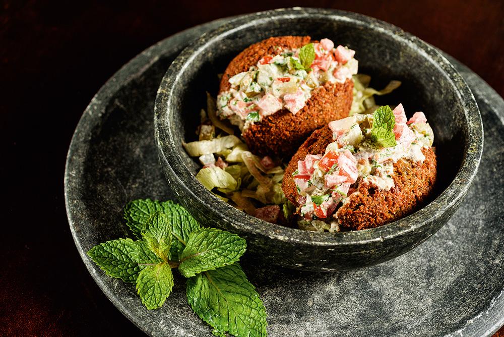 Cumbuca sobre prato de pedra com dois faláfeis recheados do restaurante Shahiya.