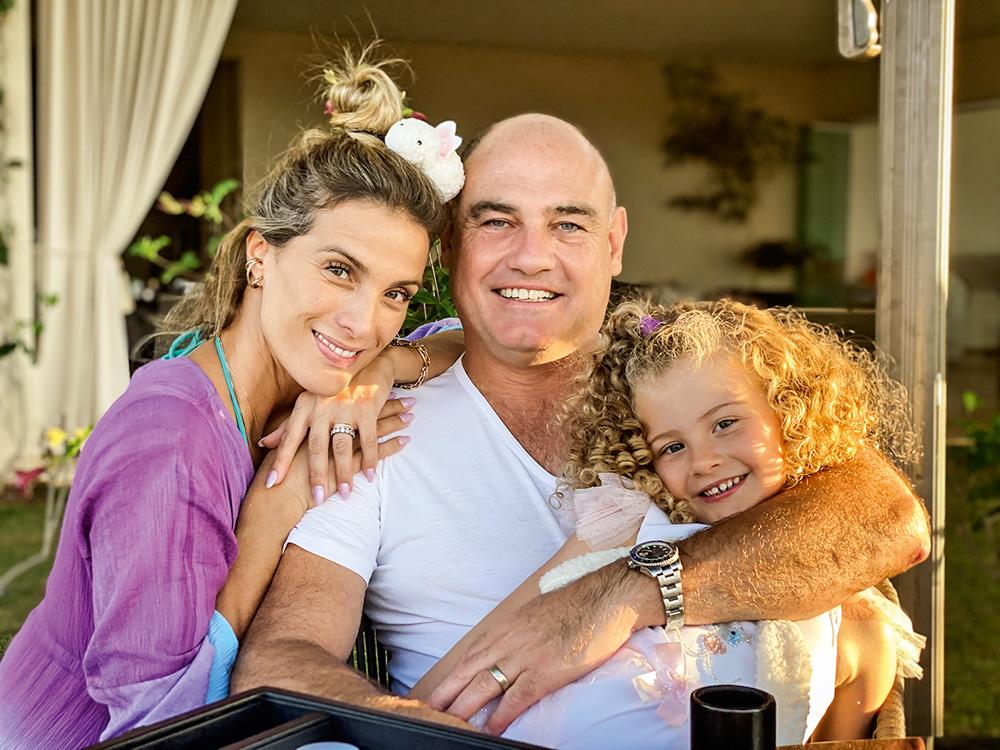 Rebecka Lima Hahn posando para a foto com a filha, Rebeckinha, e o marido, Marcelo