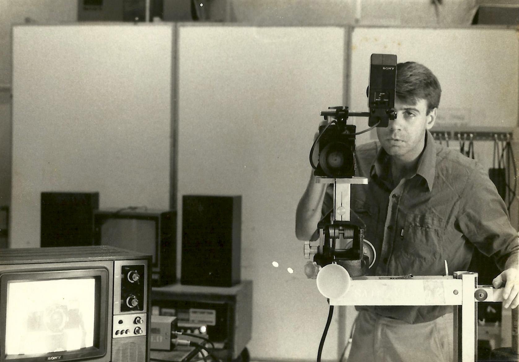 A imagem mostra Rafael usando uma câmera, com um olho nela e outro fora.