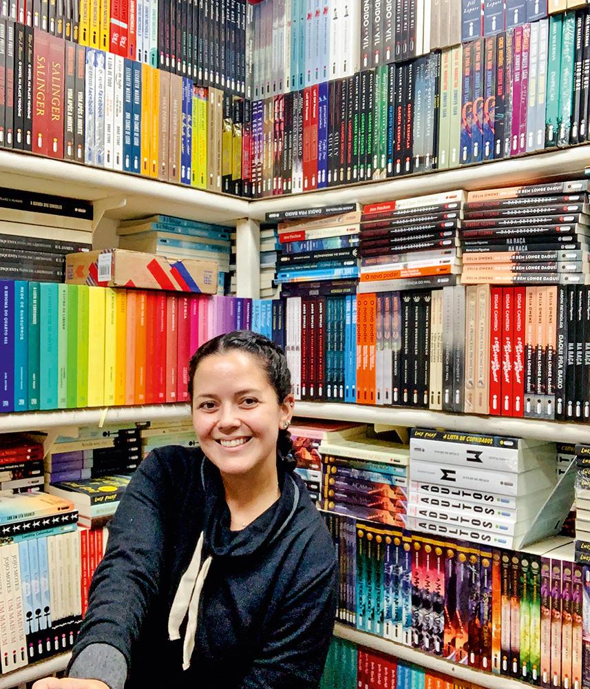 Heloiza Daou sentada posando para a foto junto de estantes repletas de livros ao fundo.