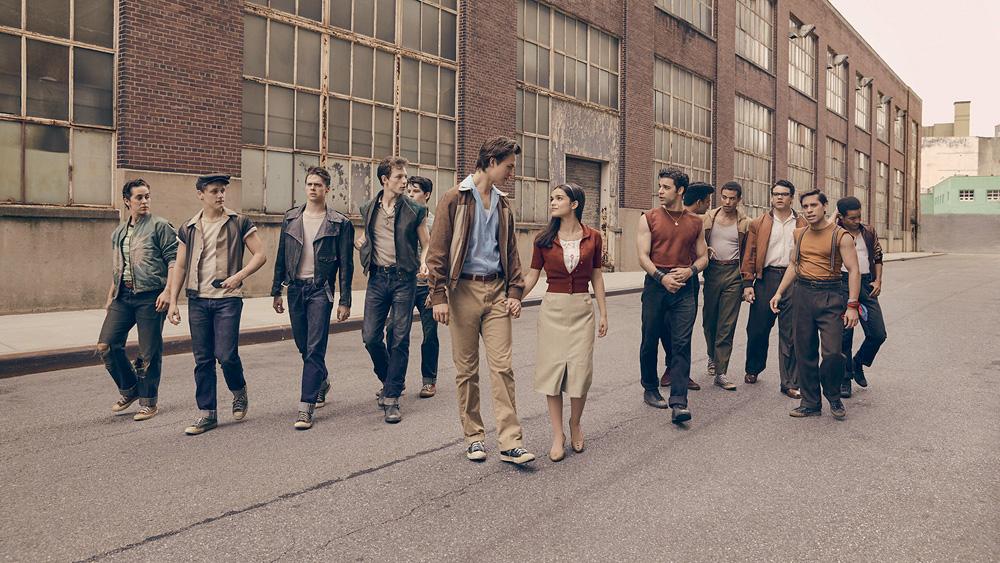 A imagem retrata uma cena do filme de Spielberg em que os personagens estão andando na rua com roupas típicas da época
