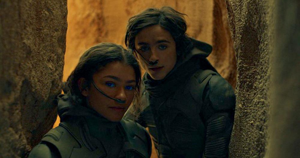 A imagem mostra Zendaya e Timothée, em Duna, estão em um cenário cavernoso, com uma expressão de alerta no rosto