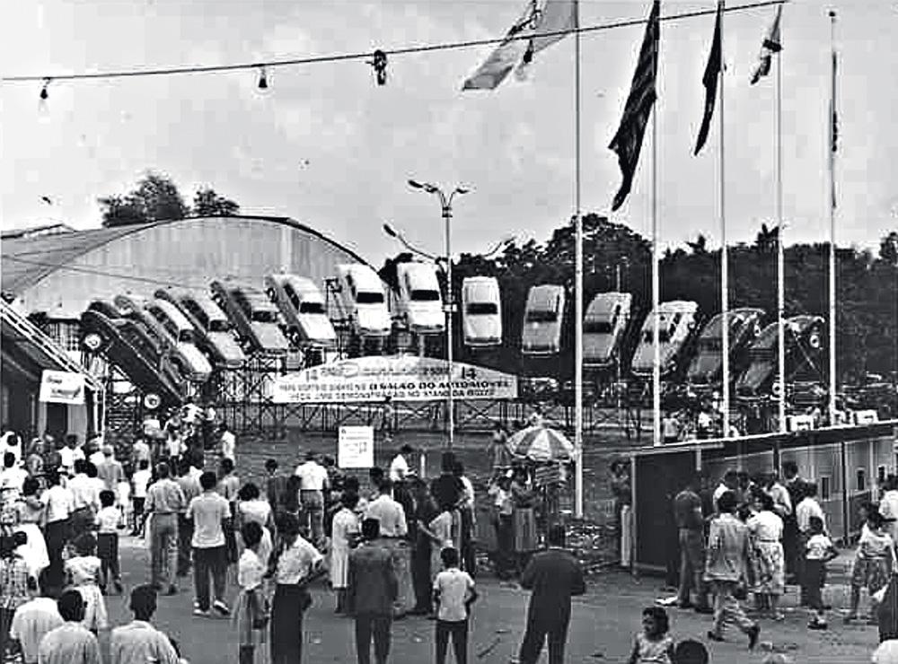 A imagem em preto e branco mostra a entrada do salão do automóvel. É uma fachada lotada de pessoas e, ao fundo, há carros erguidos com a frente voltada para o chão.