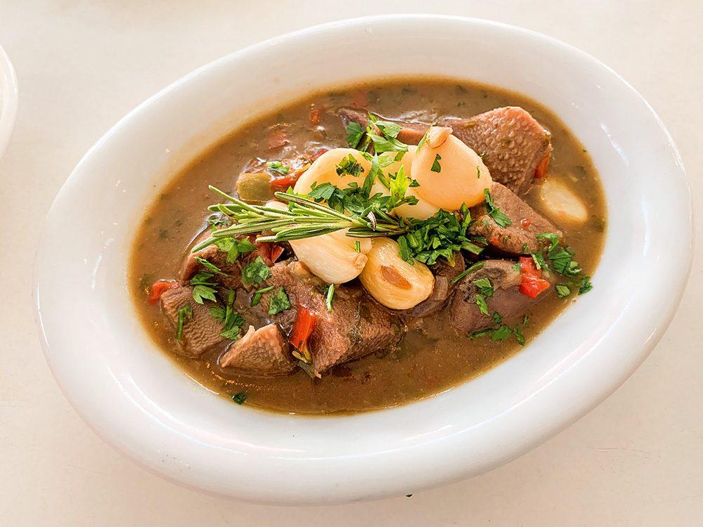 Prato oval branco sobre mesa branca com língua ao molho da própria carne coberta por dentes de alho e ervas frescas.