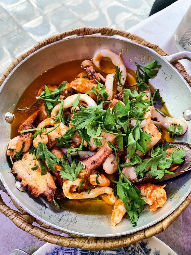 Prato com mix de frutos do mar (polvo, lula, camarão e mexilhão) coberto por coentro fresco, servido em uma panelinha de metal.