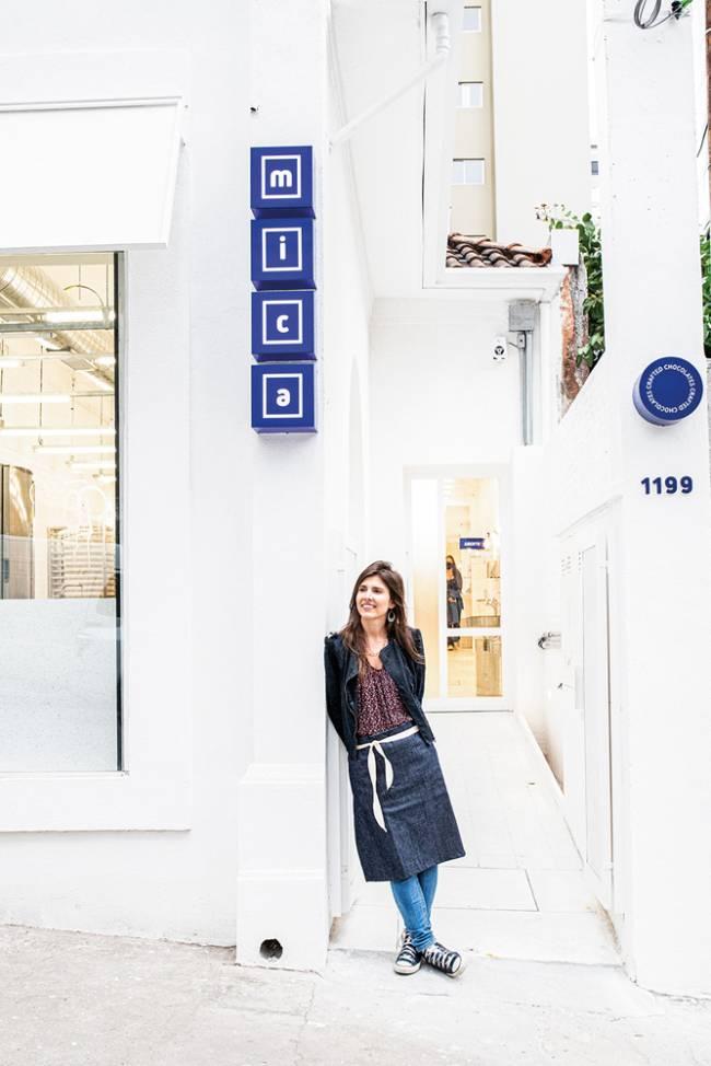 Michelle Kallas em frente à fachada toda branca da loja Mica Crafted Chocolates. Acima dela lê-se