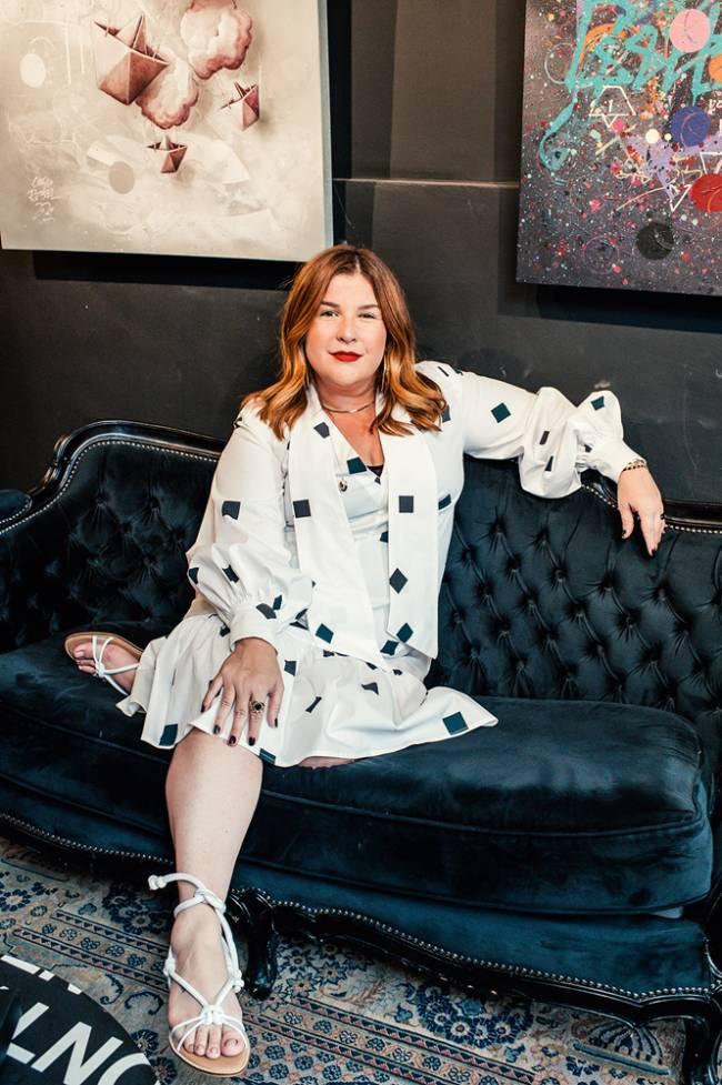 Mulher ruiva posa em um sofá preto