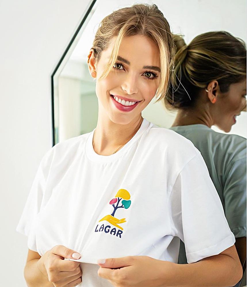 Carolina Dias Leite posando para a foto destacando com as mãos sua camisa