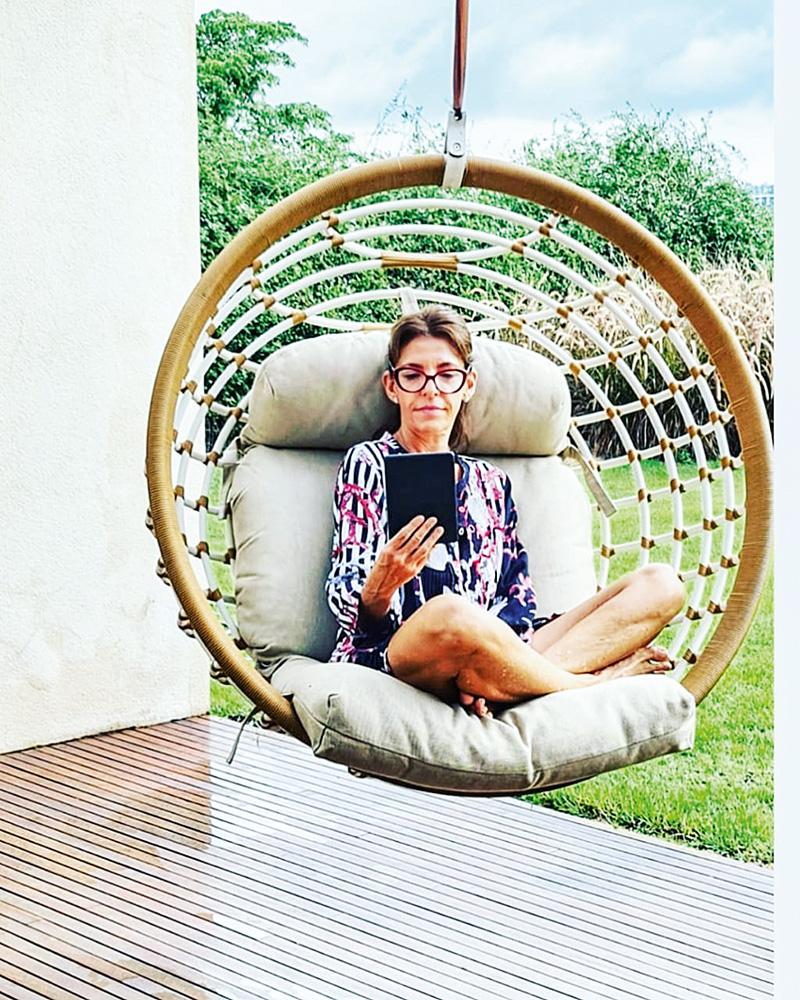 A imagem mostra Ligia Danesi sentada em um sofá exótico perto da área externa da sua casa enquanto mexe em um tablet com a mão esquerda.
