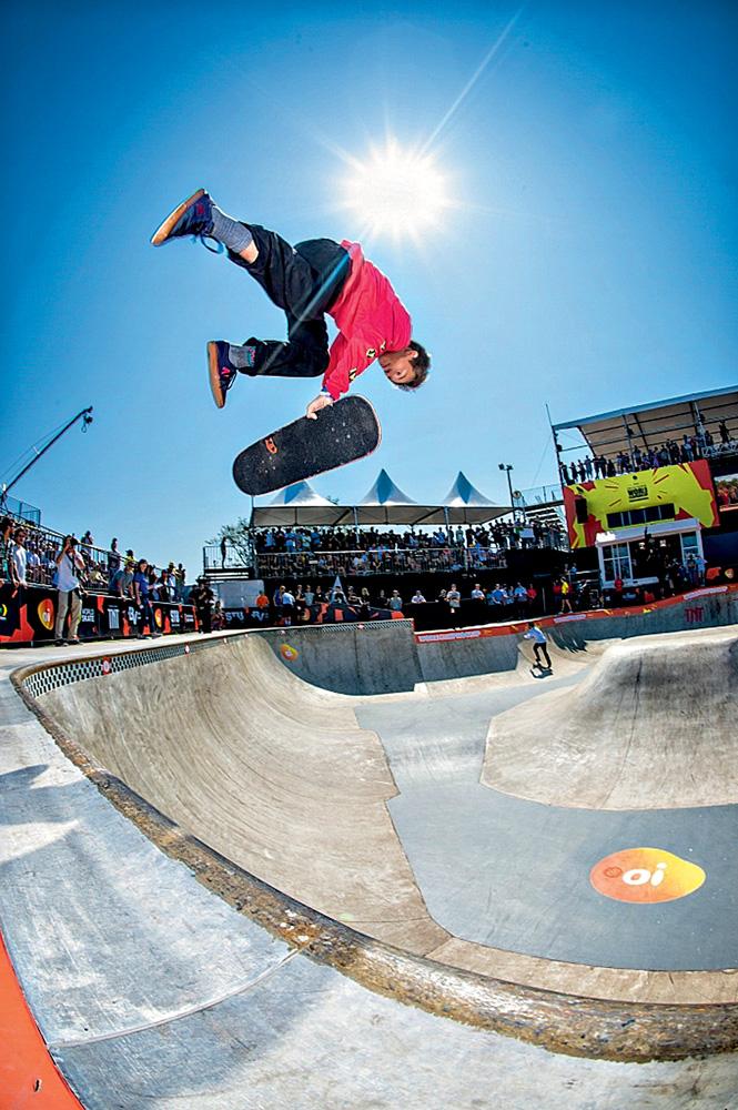A imagem mostra Luizinho fazendo uma manobra de skate em uma pista rodeada de espectadores durante um dia ensolarado.