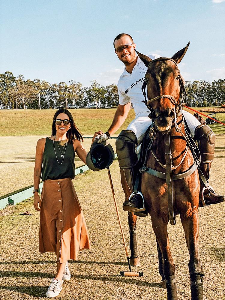 Na imagem, Napoli está em cima de um cavalo de mãos dadas com Luara, que está de pé ao lado do animal. Com um dia ensolarado, ambos estão de óculos escuros.
