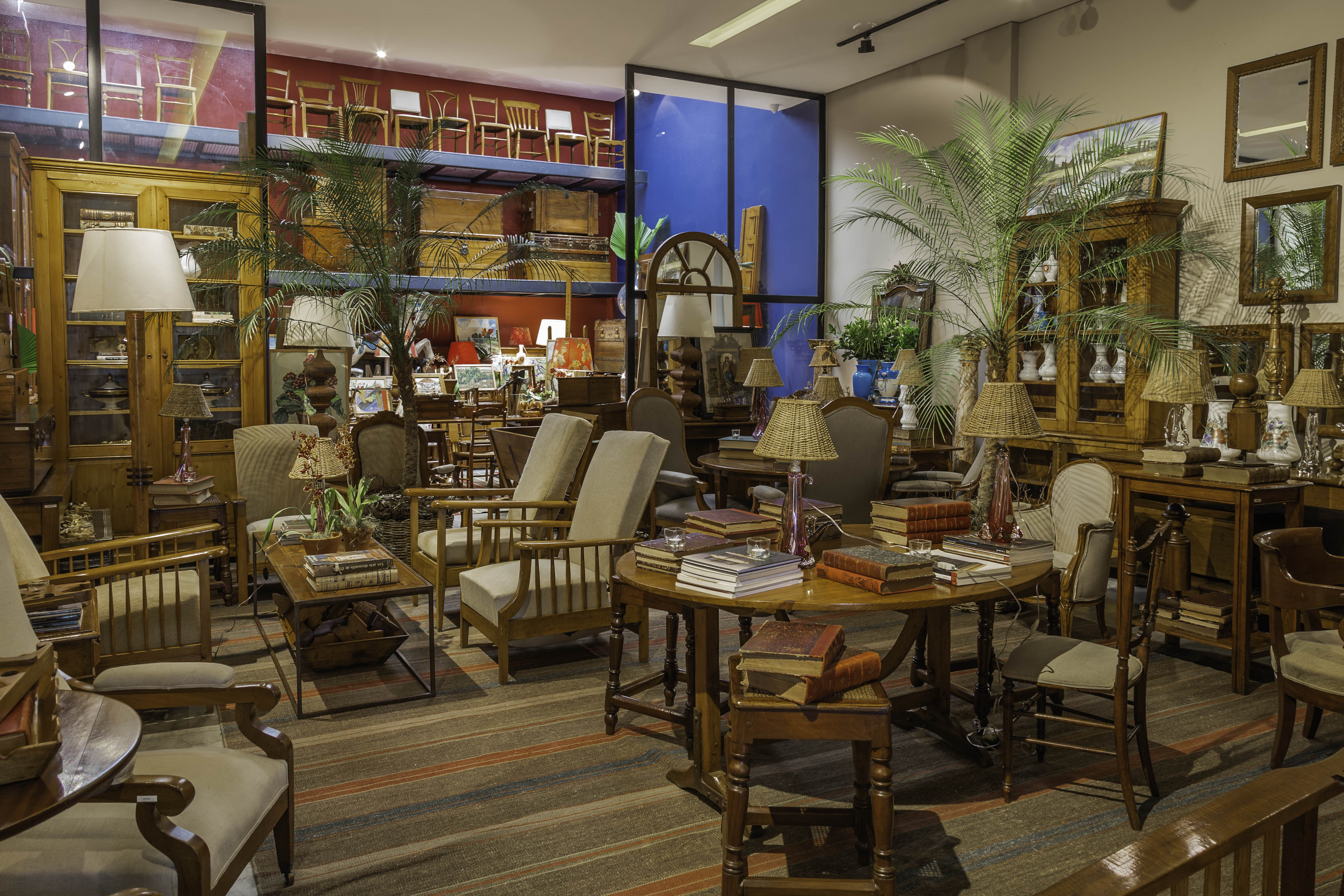 Espaço de antiquário exibe mesa de madeira escura, poltronas e diversos objetos antigos.