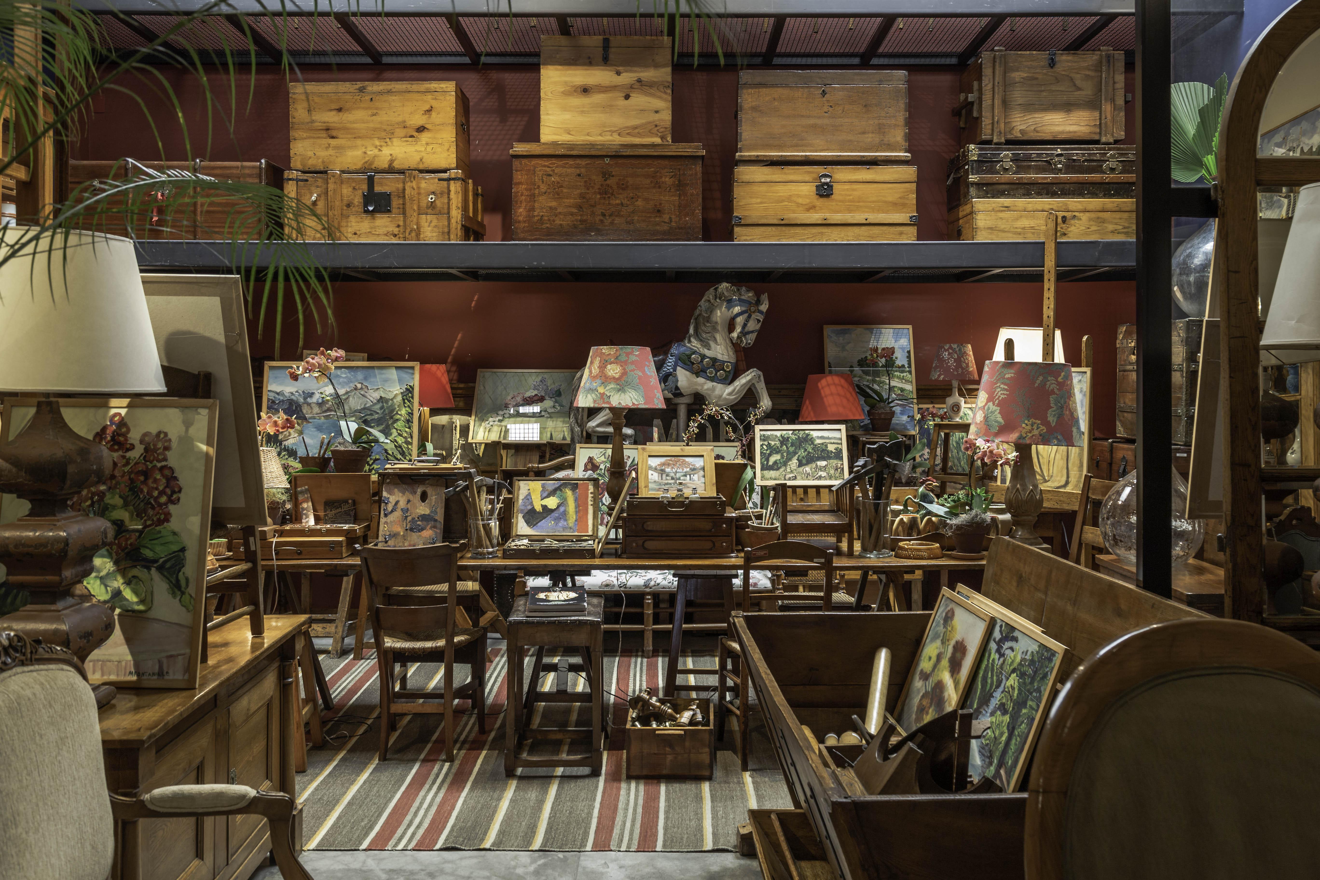 Espaço de antiquário exibe mesas e cadeiras de madeira escura, baús e um grande tapete.