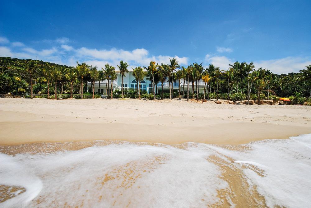 A imagem é vista a partir do mar, na praia. Nela, dá para ver no horizonte entre várias árvores uma mansão bem na margem da areia.