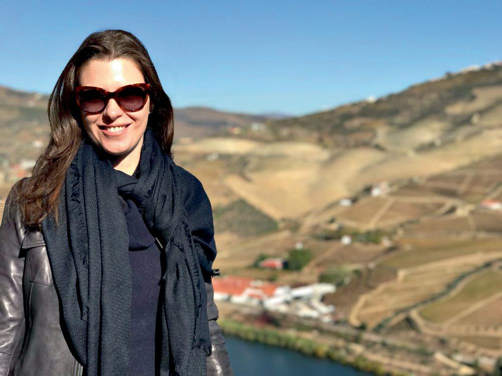mariana sorri para a foto com uma paisagem montanhosa de fundo. usa óculos escuros e cachecol.