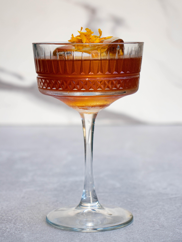 Taça de vidro em estilo coupé sobre bancada cinza com fundo branco, preenchida por drinque ambar e gelo