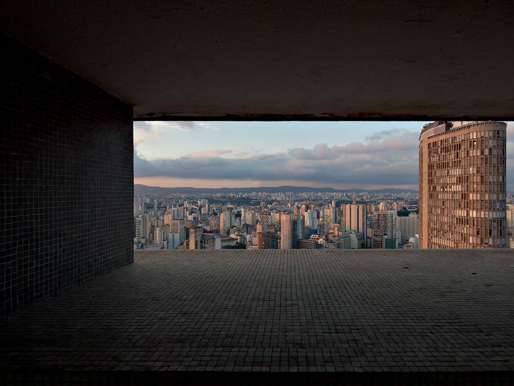 A imagem mostra a vista do 31° andar do Copan, podendo ver um horizonte repleto de prédios da cidade de São Paulo