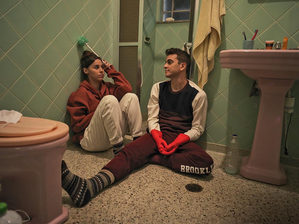 A imagem mostra Victor Lamoglia e Thati Lopes sentados no chão de um banheiro, olhando um para o outro em cena do filme