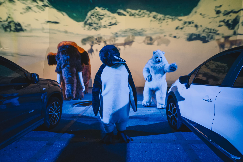 Bonecos de pinguim, mamute e urso polar em frente a dois carros e telão com imagens de neve
