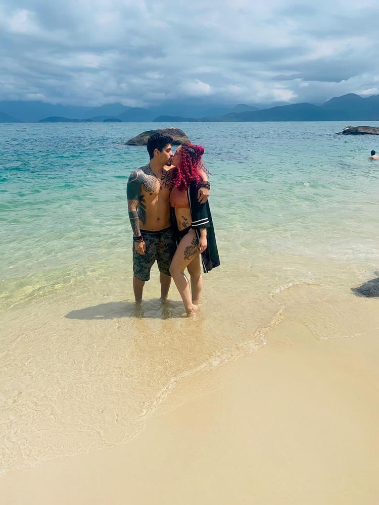 Rodrigo e Juliana na praia, na beira do mar, dando um beijo