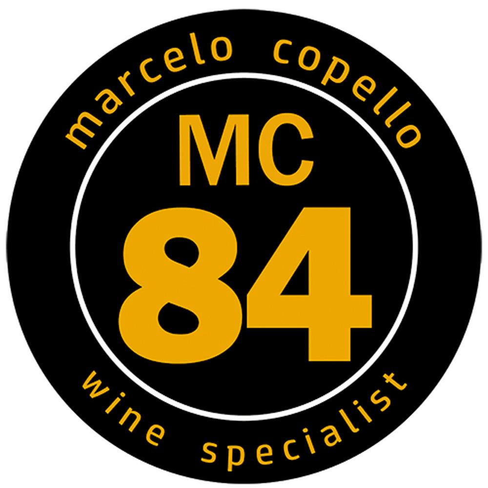 """Círculo preto em fundo branco com escritos em amarelo. Na parte superior, lê-se Marcelo Copello em caixa baixa, ao centro as iniciais MC seguidas pelo número 84 em destaque abaixo e na parte inferior, """"wine specialist"""". Selo de qualidade e vinhos do crítico Marcelo Copello."""