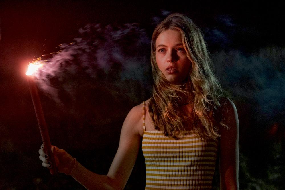 A imagem mostra Olivia Welch segurando um sinalizador durante cena do filme Panic