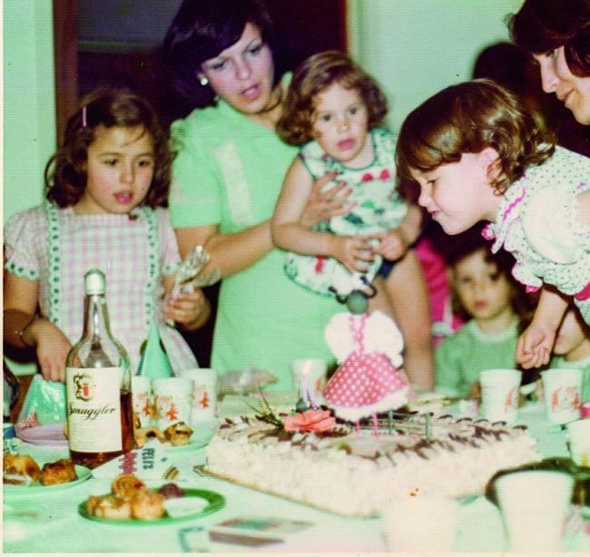 Família reunida ao redor de mesa com bolo de aniversário ao centro. Criança segurada por um adulto (à direita) sopra a vela do bolo.