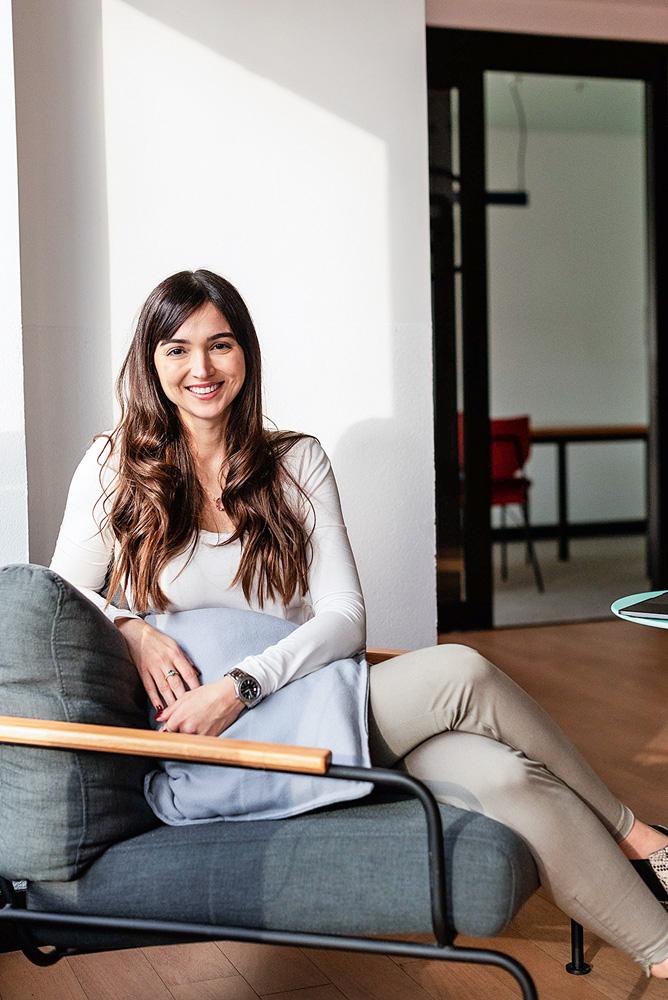 Paula Sampaio sentada em um sofá sorrindo para a foto de pernas cruzadas. Vestes camiseta branca de manga longa e calça bege.