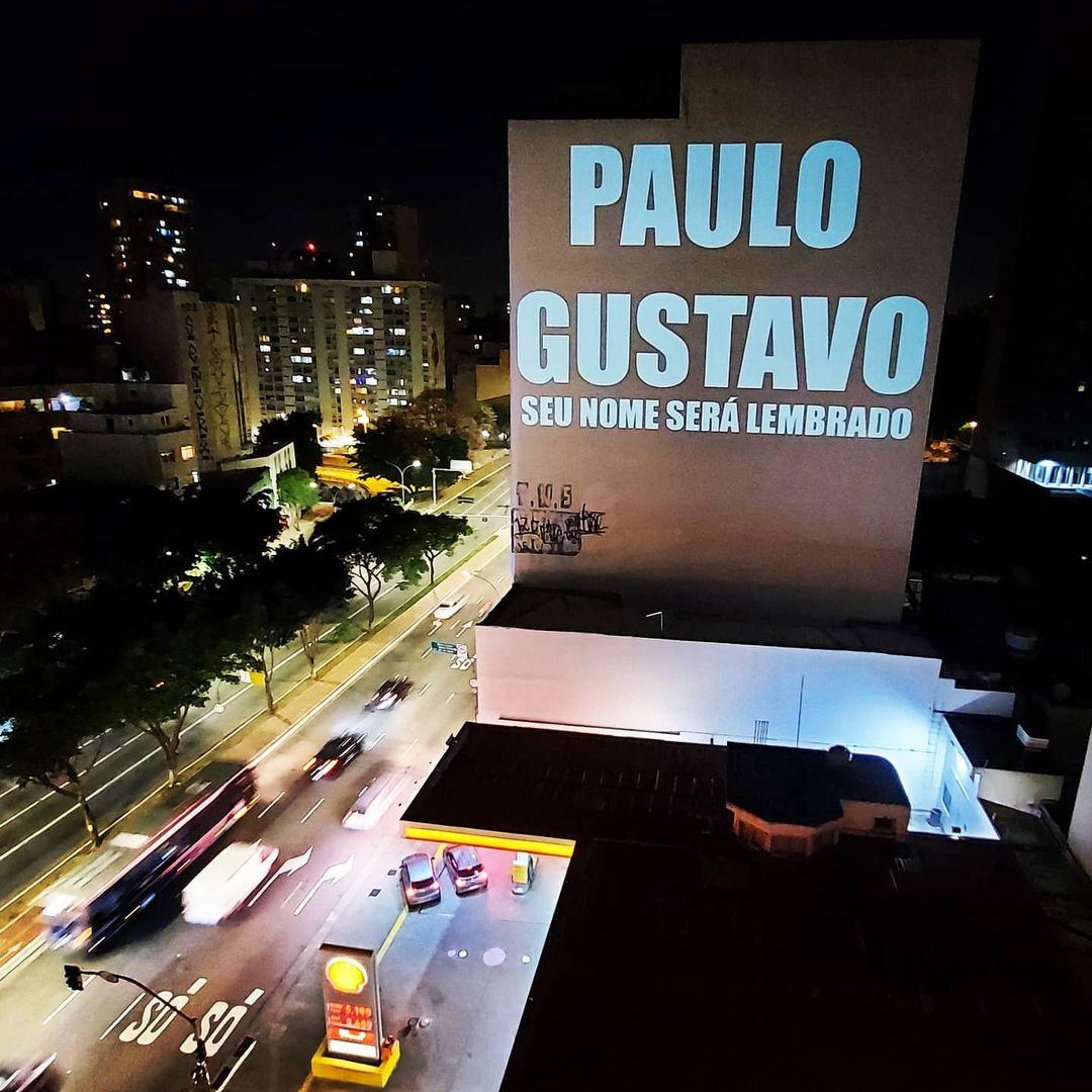 A imagem mostra um prédio no Centro de São Paulo com o nome de Paulo Gustavo projetado nele além da frase