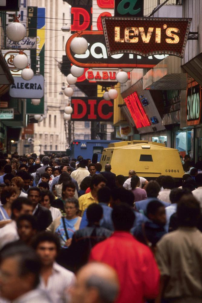 foto da rua direita, lotada de pessoas, com diversas placas de anúncio de marcas sobre suas cabeças