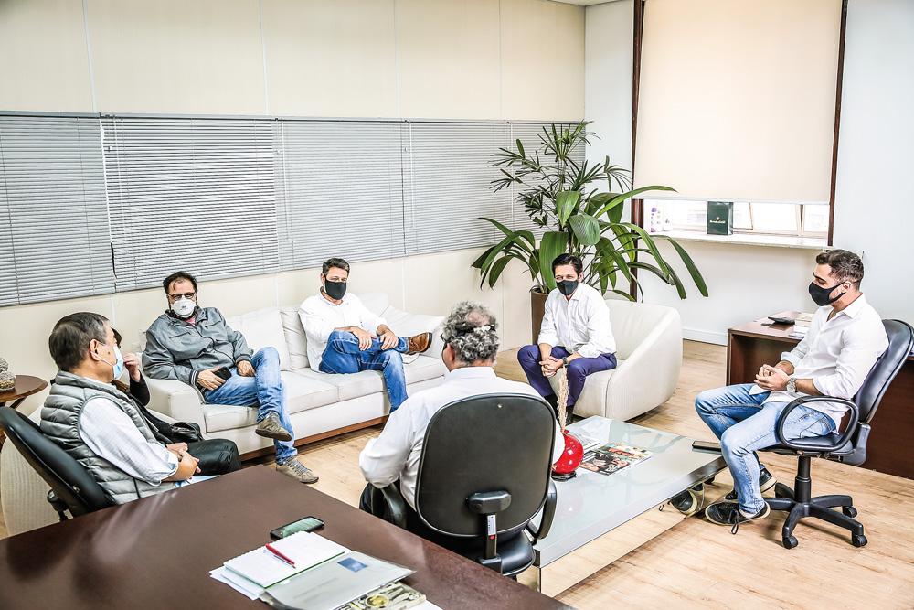 A imagem mostra Ricardo Nunes e seus secreta´rios em uma sala, todos de máscara, durante uma reunião. Eles estão sentados em sofás e cadeiras, relativamente distantes