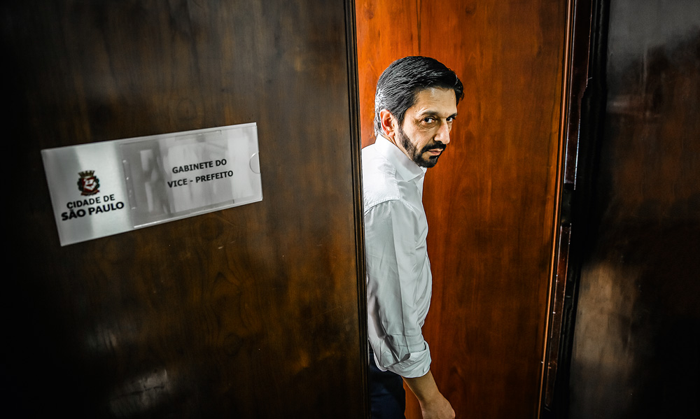 A imagem mostra Ricardo Nunes parado na porta de seu gabinete. Ele está a abrindo e há um pequeno letreiro escrito