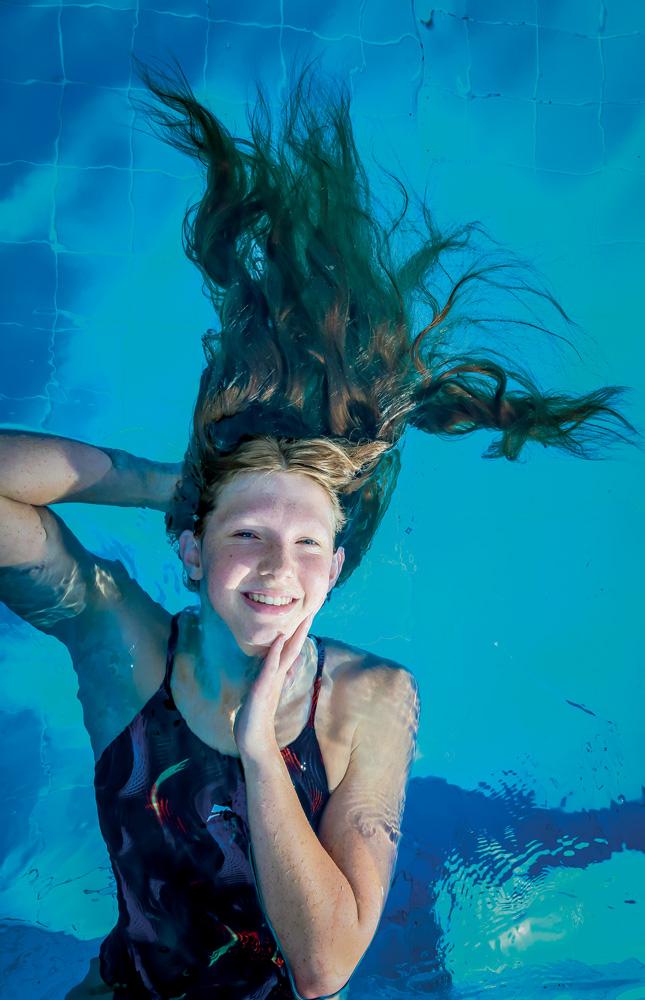 A imagem mostra Stephanie boiando em uma piscina. A câmera a vê de cima, e ela está sorrindo para a foto com todo o corpo submergido com exceção do rosto.
