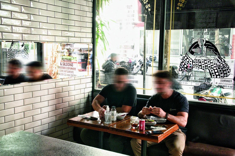 Dois homens sentados comendo em mesa de madeira ao centro da imagem, em frente a janelão de vidro que dá para a rua.