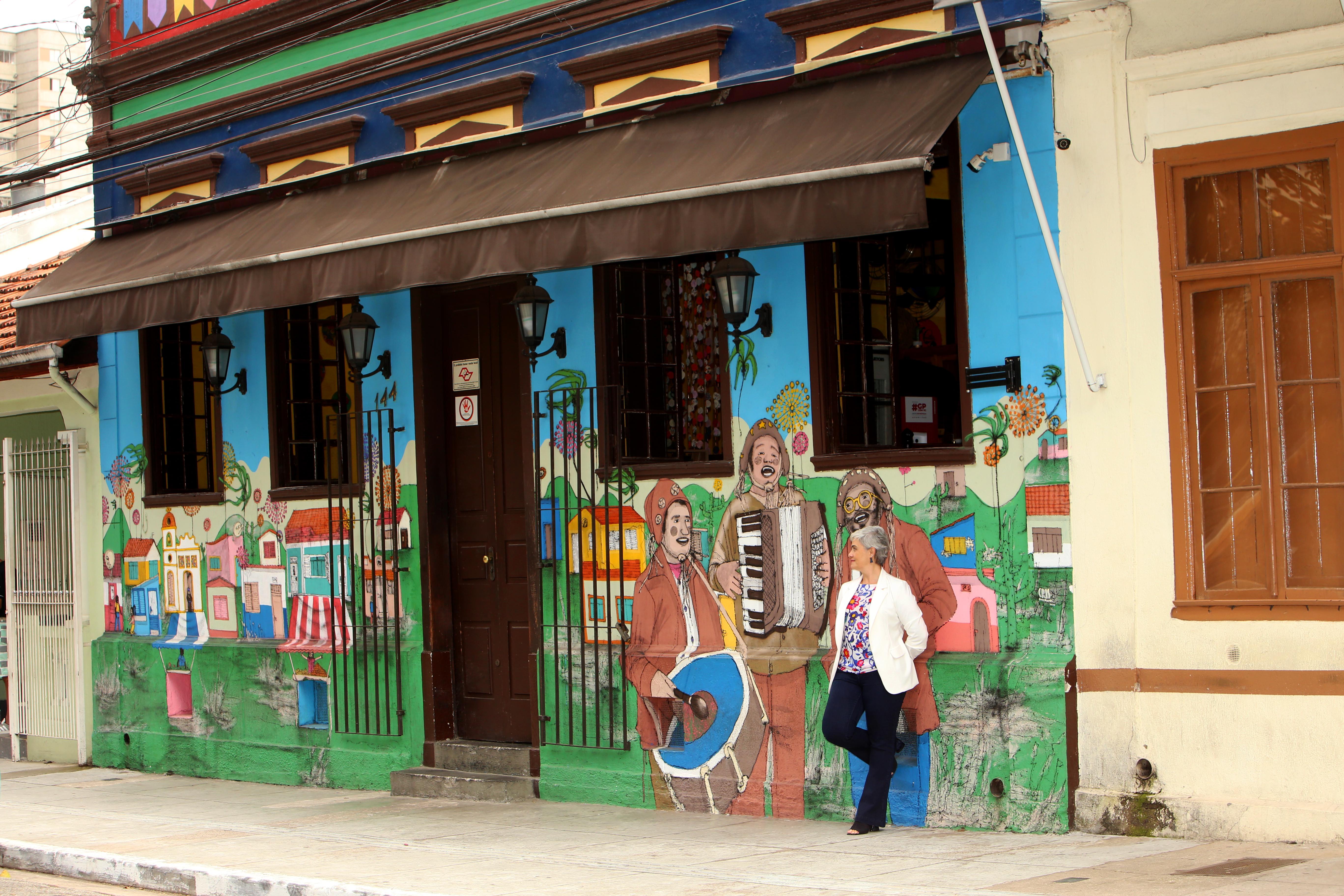 A vereadora Sandra Santana aparece de longe, encostada em parede colorida de restaurante na Freguesia do Ó. Veste calça preta e blazer branco.