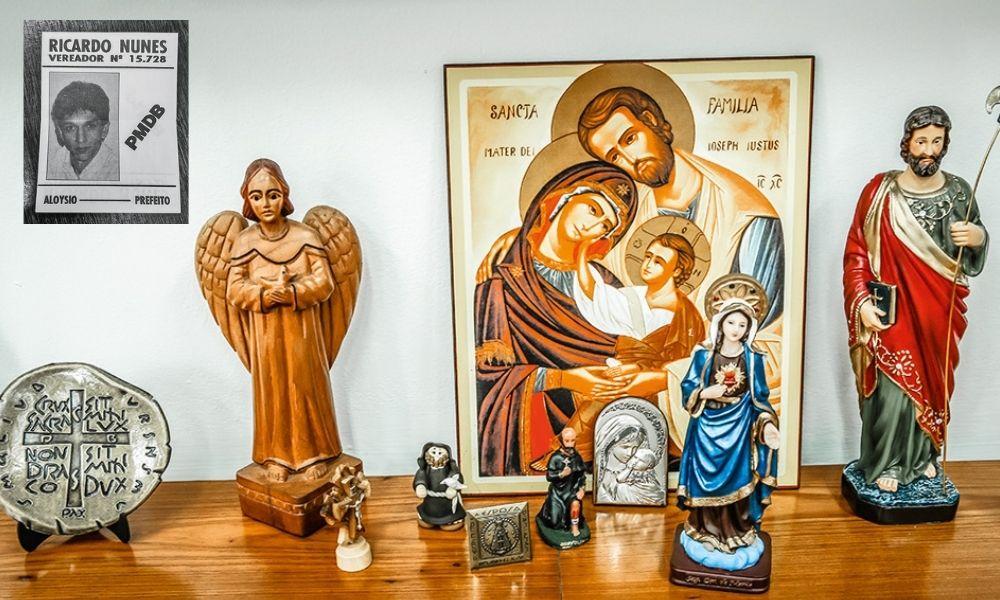 A imagem mostra figuras religiosas em uma mesa de madeira. Mais a cima, uma pequena foto de Nunes, ainda jovem, em uma cartaz escrito