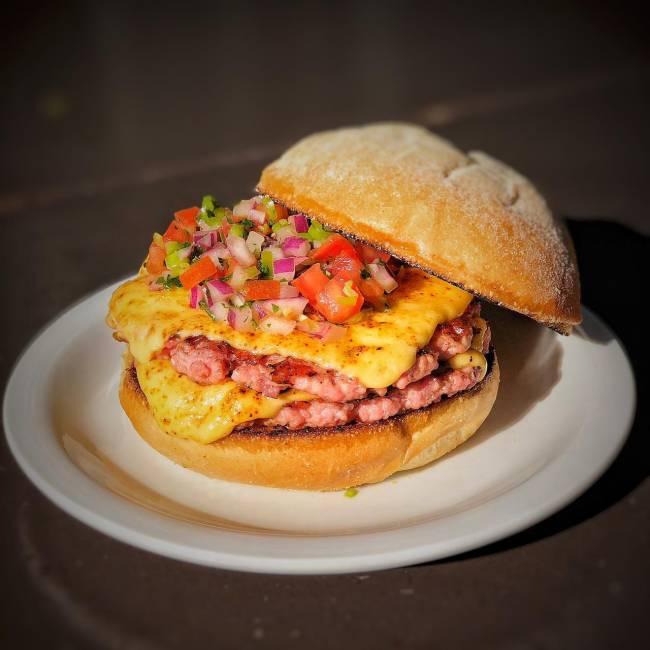 Hambúrguer sobre prato de louça branca em cima de mesa de madeira. Dois discos suínos (rosados) com queijo e vinagrete por cima, com o pão superior afastado para o lado.
