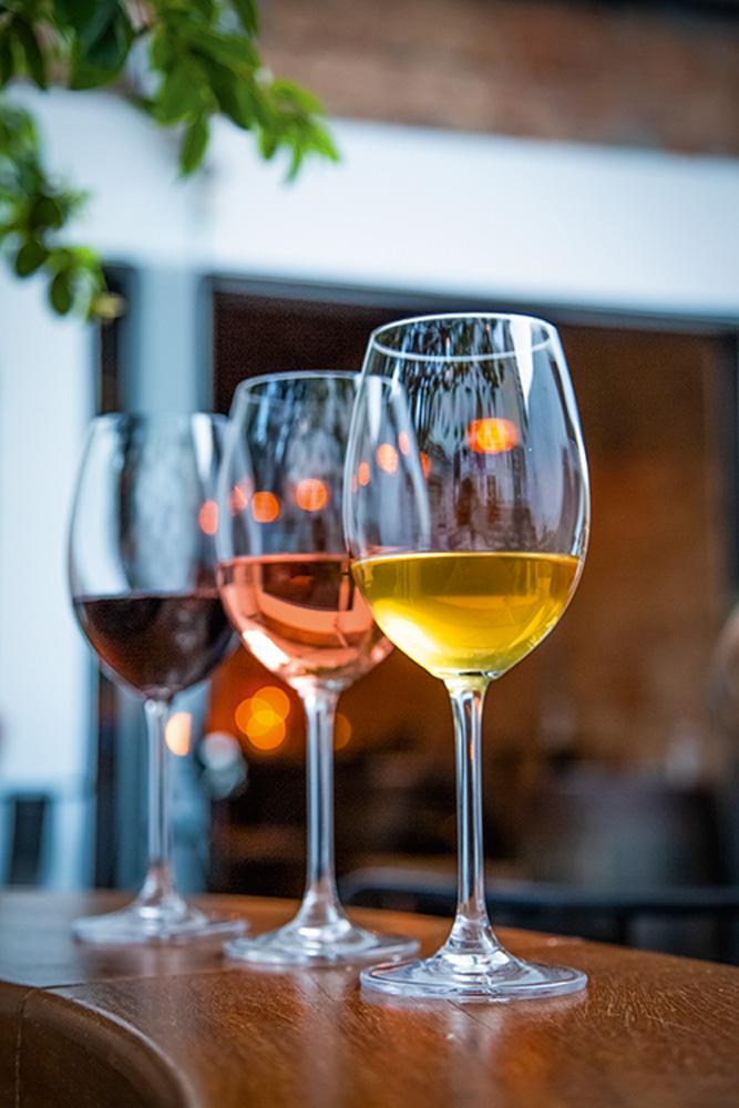 Três taças de vinho em sequência sobre tampo de madeira. Em primeiro plano vinho branco alaranjado, seguido por rosé e tinto.